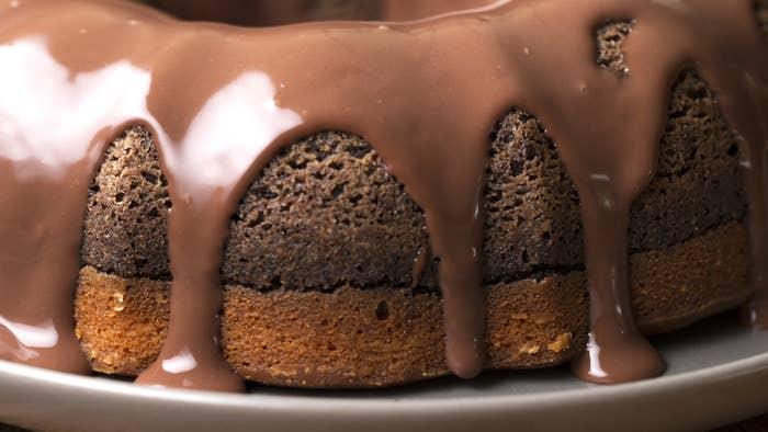 1. Preaqueça o forno a 180°C.2. Para o brownie: em uma tigela misture a manteiga, o açúcar, o cacau e os ovos até ficar homogêneo. Adicione a farinha e o bicarbonato e misture bem.3. Transfira para uma forma redonda de 21cm de diâmetro untada e enfarinhada e espalhe bem.4. Leve ao forno por 25 minutos. Reserve.5. Para o bolo de cenoura: no liquidificador bata as cenouras, os óleo, os ovos e o açúcar até ficar uniforme. Adicione a farinha e o fermento e bata só até tudo se misturar.6. Coloque a massa do bolo de cenoura sobre o brownie pré-assado.7. Volte ao forno por 45-50 minutos ou até você inserir um palito no meio do bolo e ele sair limpo. Deixe esfriar por 10 minutos antes de desenformar.8. Em outro recipiente misture o chocolate e o creme de leite. Leve ao micro-ondas por 1 minuto e 30 segundos, em intervalos de 30 segundos em potência média.9. Despeje a calda sobre o bolo.10. Sirva com mais calda.Aproveite!