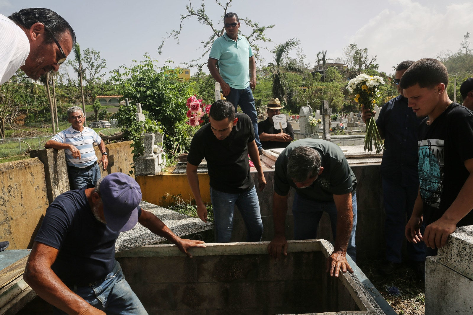 Mourners and cemetery workers gather at the gravesite on Oct. 19 in Utuado, Puerto Rico.