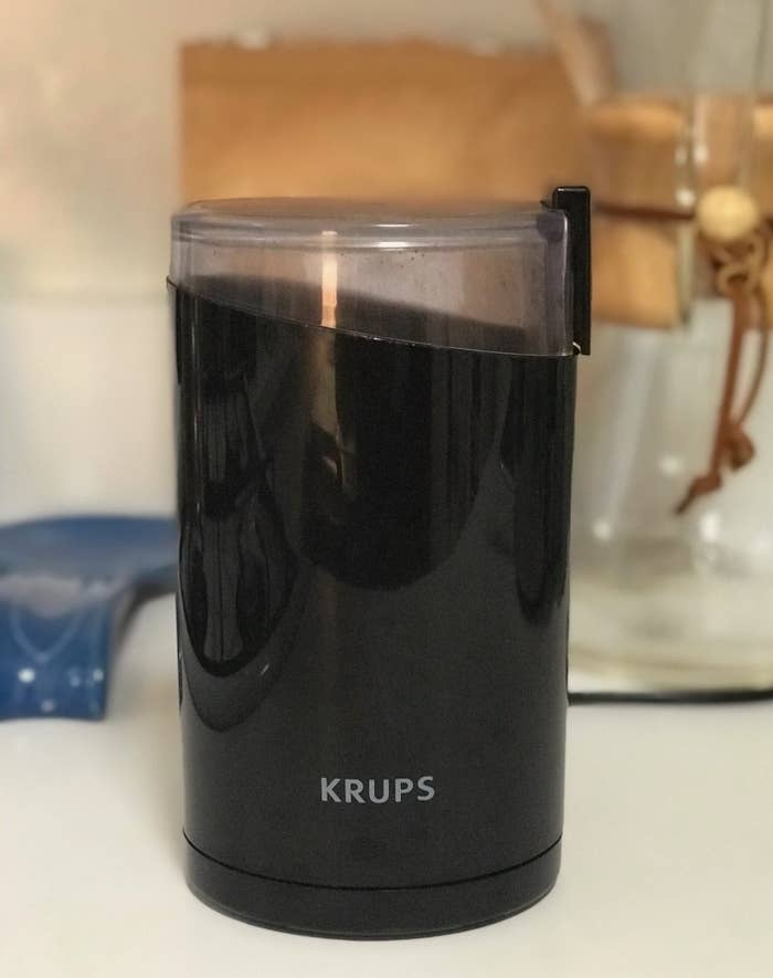 The black cylinder coffee grinder on a kitchen countertop