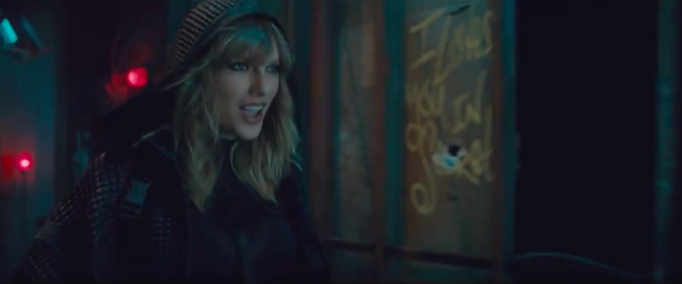 """Then she struts down an alleyway covered in graffiti that says mysterious things like """"I love you in secret""""."""