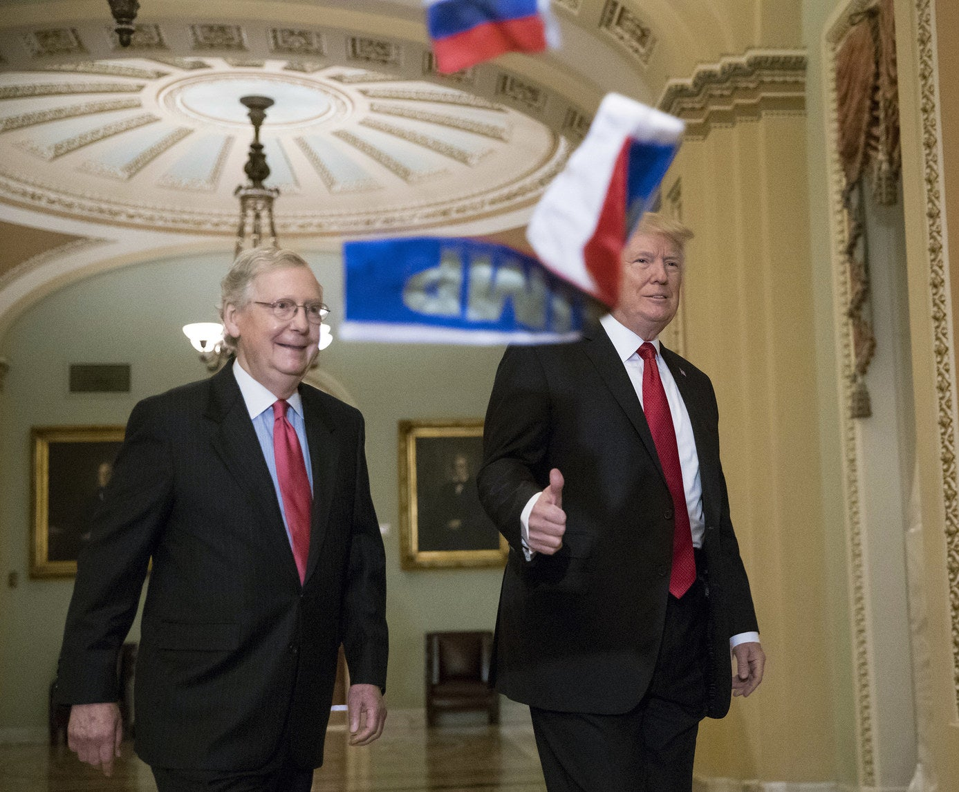 Protesters throw small Russian flags at President Trump and Sen. Majority Leader Mitch McConnell on Capitol Hill, Oct. 24.