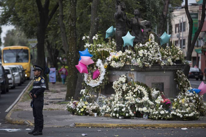 A police officer directs traffic near a memorial honoring 19 children and seven adults who died when a wing of a school collapsed in the earthquake.