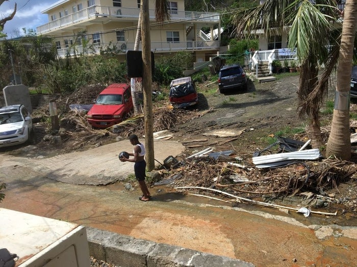 Guyma Phebe plays basketball amid hurricane debris in a neighborhood in St. John.