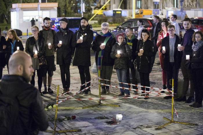 People hold a vigil in Warsaw where a man set himself on fire.