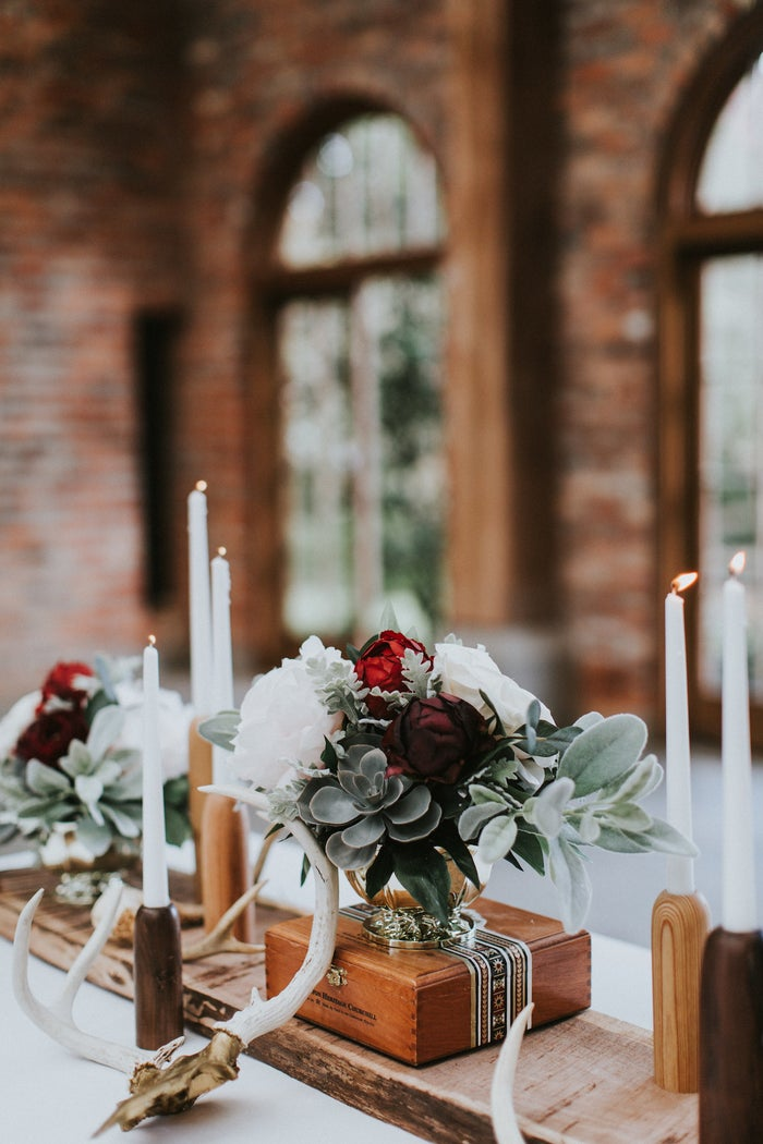 Fall is all about moody, unexpected floral arrangements. Something Borrowed Blooms, a premium silk-flower Rent & Return floral boutique, mixed deep hues, soft pale colors and textured succulents like red hen to create an interesting and unexpected centerpiece.