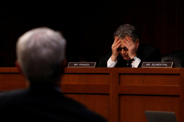 Sen. Al Franken buries his head in his hands after an exchange with Facebook General Counsel Colin Stretch.