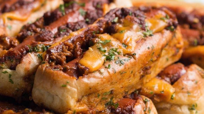 Rendimento: 8Você vai precisar de:1 pacote com 8 pães de cachorro-quente¼ de xícara de manteiga derretida2 dentes de alho amassados2 colheres de sopa de salsa picada fininha8 fatias de queijo cheddar8 colheres de sopa de chili cozido1 pacote de 500g de salsichasModo de preparo:1. Preaqueça o forno a 180°C.2. Coloque os 8 pães de cachorro-quente em uma assadeira de 23x33 centímetros, corte um retângulo em cada pão de cachorro-quente, certificando-se de manter a 1 centímetro das bordas.3. Aperte a parte cortada de cada pão firmemente para baixo, certificando-se de apertar as bordas inferiores também. Isso ajudará a criar um espaço maior para os recheios e evitar que eles transbordem.4. Misture a manteiga, o alho e a salsa em uma bacia pequena, e depois passe essa mistura nos pães e em suas aberturas.5. Leve ao forno por 5 minutos para tostar os pães e ajudar as laterais dos pães a firmarem para que não abram com o peso dos recheios.6. Coloque uma fatia de queijo cheddar em cada pão e, depois, coloque um pouco do molho de pimenta.7. Coloque a salsicha por cima do molho de pimenta e, depois, cubra com mais molho.8. Leve ao forno por 20-25 minutos, até o queijo dourar e o molho de pimenta começar a dourar.9. Separe os cachorros-quentes abertos com a faca e tenha um bom apetite!