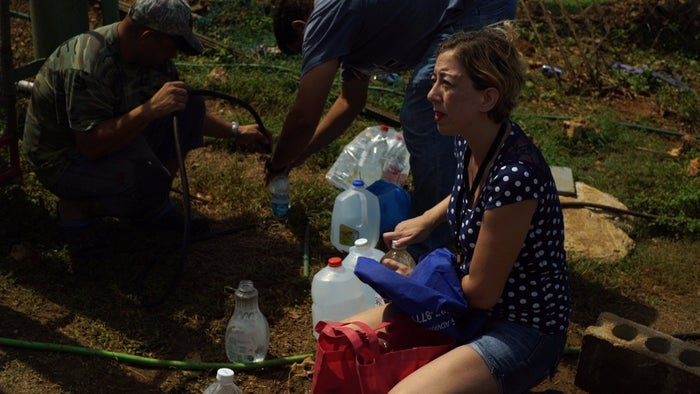 Lynette Caban fills up water jugs from a house attached to a mountain spring in Arecibo.