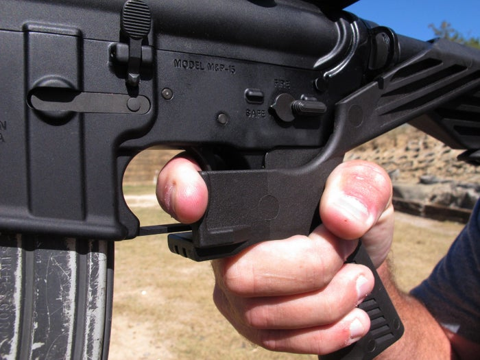 """Shooting instructor Frankie McRae illustrates the grip on an AR-15 rifle fitted with a """"bump stock"""" at his 37 PSR Gun Club in Bunnlevel, North Carolina."""