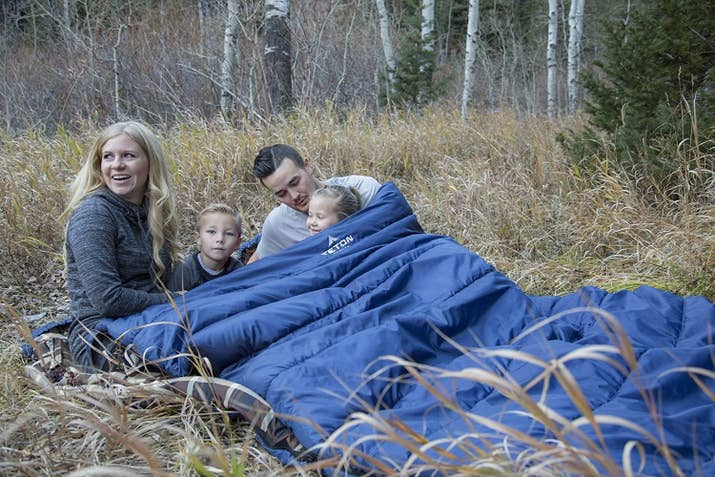 """This 20°F sleeping bag is more than enough for a couple to spread out in. It opens up at 94""""x62"""" (27""""x14"""" when packed up) and weighs 14 lbs. It has a taffeta shell and a flannel liner. It also unzips on each side AND the bottom for easy access and ventilation. The zipper and shoulder draft tubes keep the cold air out. Promising review: """"My girlfriend and I used this bag for two months straight on our cross-country road trip around the US — it was comfier than my bed back at home! Super warm and cozy, perfect for three-season camping. I was comfortable in this thing down to 40°F in shorts and a T-shirt, and down to 32°F in a light hoodie! No issues to report after two months of heavy usage/daily packing and unpacking. Seriously considering using this thing on top of my bed now that I'm back home. Would DEFINITELY recommend!"""" —DerekPrice: $119.99+ (available in five colors and two temperature ratings)"""
