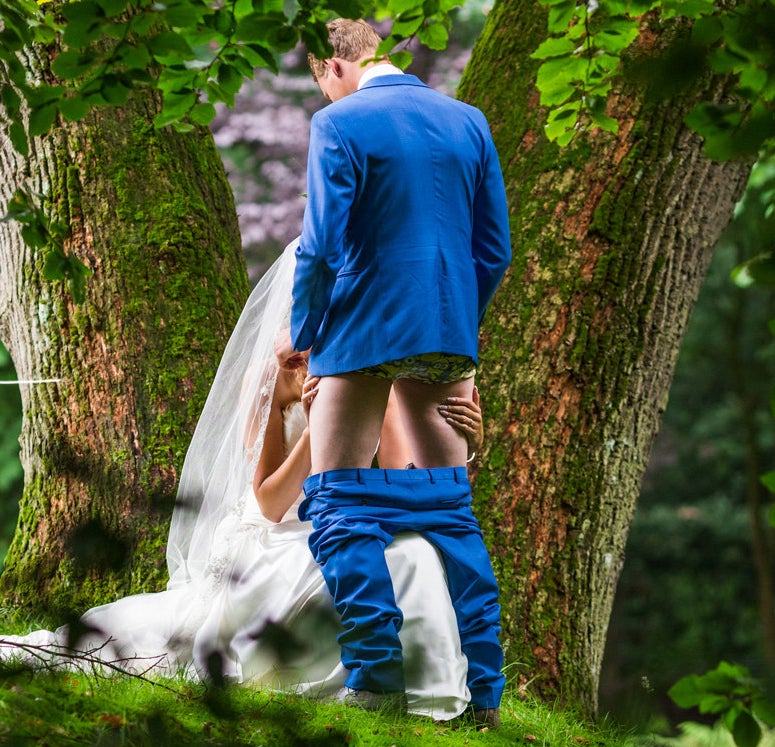 In case you're adjusting your screen, yes, it's a picture of a bride simulating giving her new husband a blow job, surrounded by the kind of gorgeous leafy trees anyone would want dotting the grounds of their wedding venue.