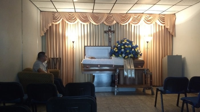 Herman Alvarez sitting by his father's casket.