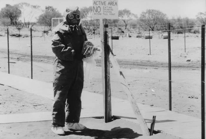 Supplied photo of John L. Stanier in the South Australian town of Maralinga wearing protective clothing (showing a camera also protected in a special plastic cover) in 1950. Maralinga was the site of British nuclear bomb testing.