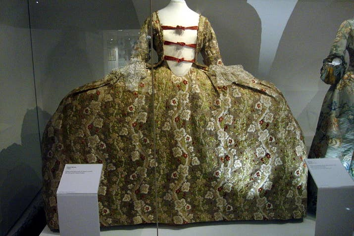 """El vestido """"pannier"""", como este ejemplo de 1760, era reforzado con largos aros laterales planos que se extendían a lo largo de la falda sin hacerla más larga en la espalda. El área grande y oblonga en el frente se convirtió en un lugar en donde las mujeres adineradas podían presumir sus bordados más elegantes. Esencialmente eran como grandes pinturas caminantes."""