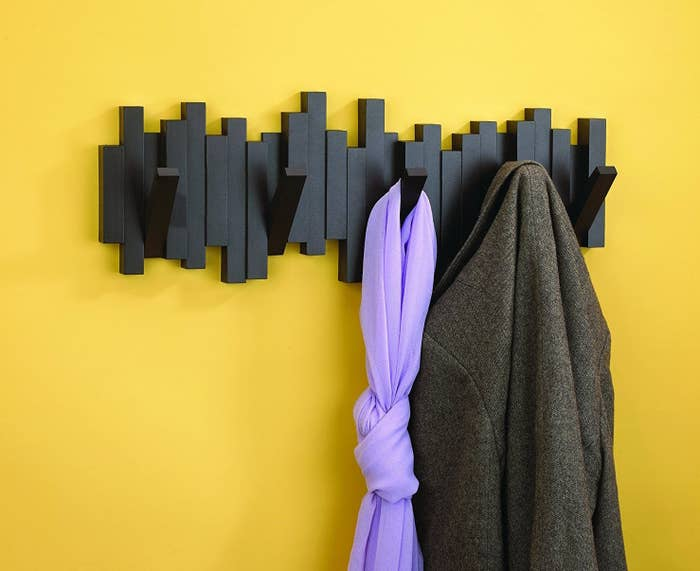 """Promising review: """"Such an original and innovative design. I got this to hang my grandkids' dress-up clothes on when they are at my house. It works perfectly, and when the kids leave and capes and princess dresses get put away, the wall hooks just fold up and the entire thing becomes a wall design. This is such a great way to have wall hooks that don't look like the same old boring thing and I love the flexibility of getting rid of the hooks when they're not needed."""" —LeahGet it from Amazon for $24.99 (three colors) or Jet for $28.97 (white) or $29.99 (black and espresso)."""