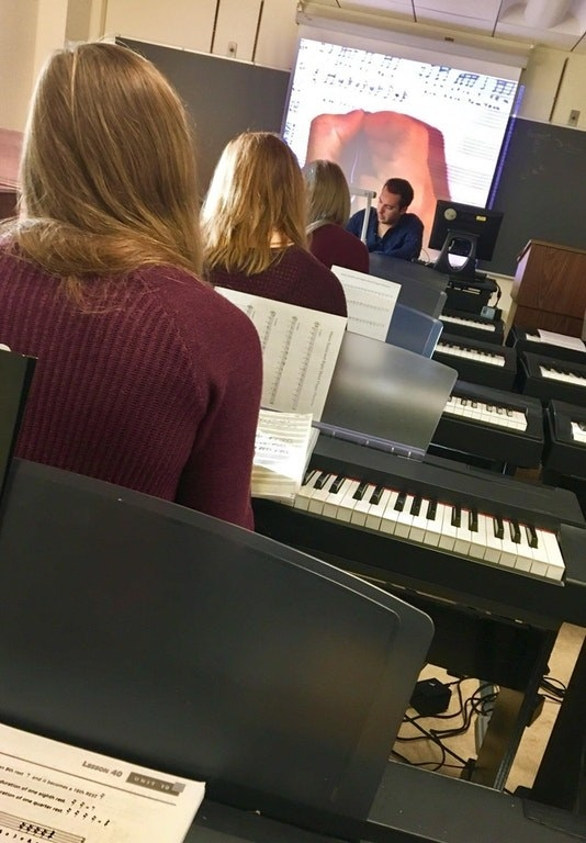 These three girls wearing the same color shirt, with the same color hair, sitting in the same row of class.