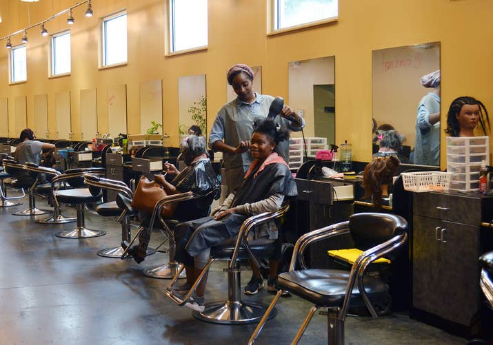 A cosmetology student works on a guest in Pro Way's salon, where student haircuts are cheap for local residents.