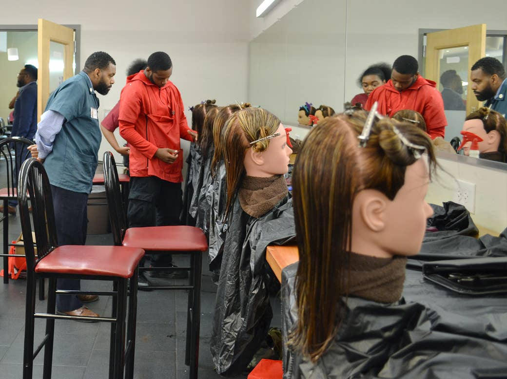 An instructor supervises a student in a freshman barbering class.