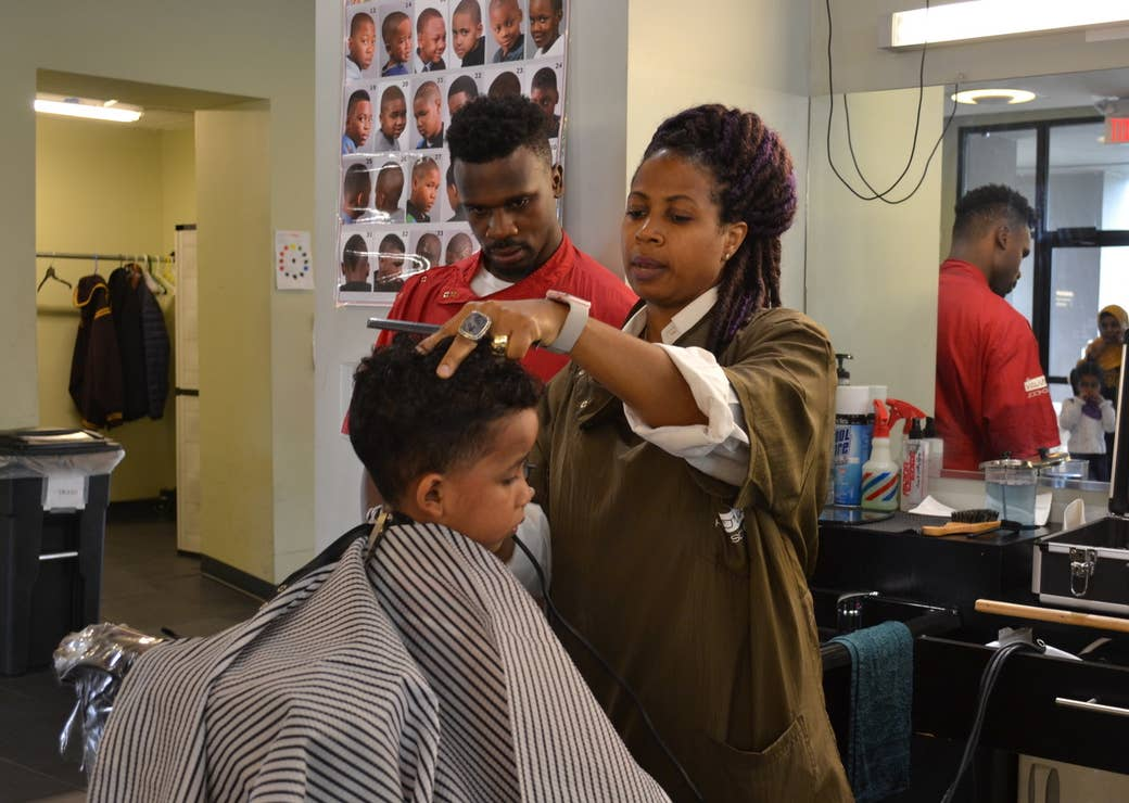 An instructor helps a student give a haircut to a little boy visiting the Pro Way barbershop.
