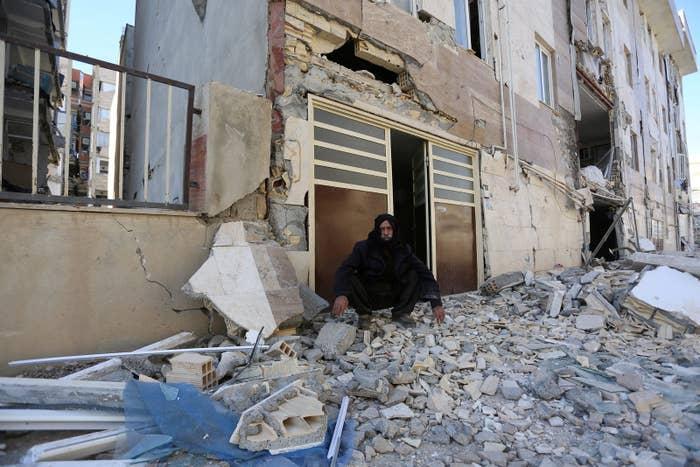 A man sits outside a damaged building following an earthquake in Sarpol-e Zahab.