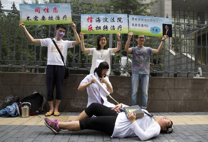 Gay rights activists act out electric shock treatment to protest conversion therapy outside a court in Beijing.