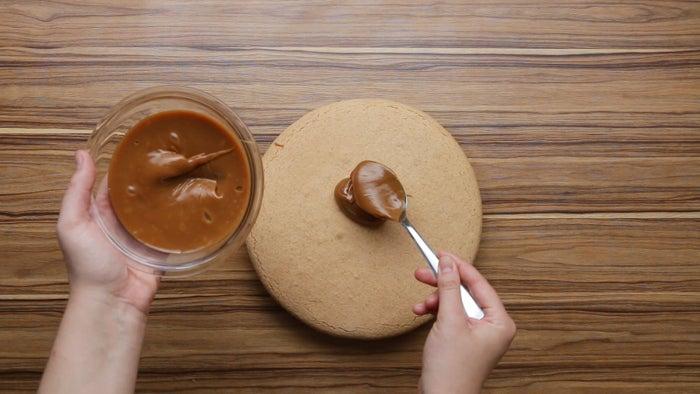 1. Preaqueça o forno a 180°C.2. Em uma tigela, misture farinha, açúcar, amido, fermento, bicarbonato, manteiga, baunilha, ovos e gemas até formar uma massa uniforme.3. Divida a massa em duas partes, embale com plástico filme e leve à geladeira por 30 minutos para firmar.4. Abra a massa sobre papel manteiga polvilhado com farinha de trigo.5. Corte um círculo de 23cm com espessura de cerca de 0,5-0,6cm. Transfira o disco com o papel manteiga para uma assadeira. Repita o processo com a outra metade de massa.6. Leve ao forno por 15-20 minutos ou até que fiquem levemente dourado. Deixe os discos esfriarem completamente.7. Passe doce de leite sobre uma das metades e coloque a outra metade por cima. Pressione delicadamente.8. Coloque o alfajor sobre uma grade e espalhe chocolate derretido por cima e nas laterais do alfajor, deixe o excesso escorrer.9. Leve à geladeira por 10 minutos para endurecer.10. Aproveite!