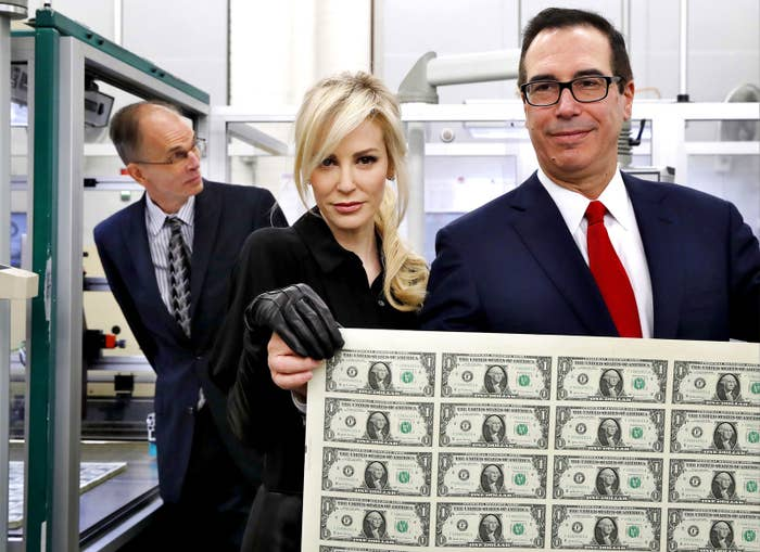 Treasury Secretary Steven Mnuchin (R) and his wife Louise Linton hold up a sheet of new $1 bills, the first currency notes bearing his and US Treasurer Jovita Carranza's signatures, at the Bureau of Engraving and Printing in Washington, DC, on Nov. 15.