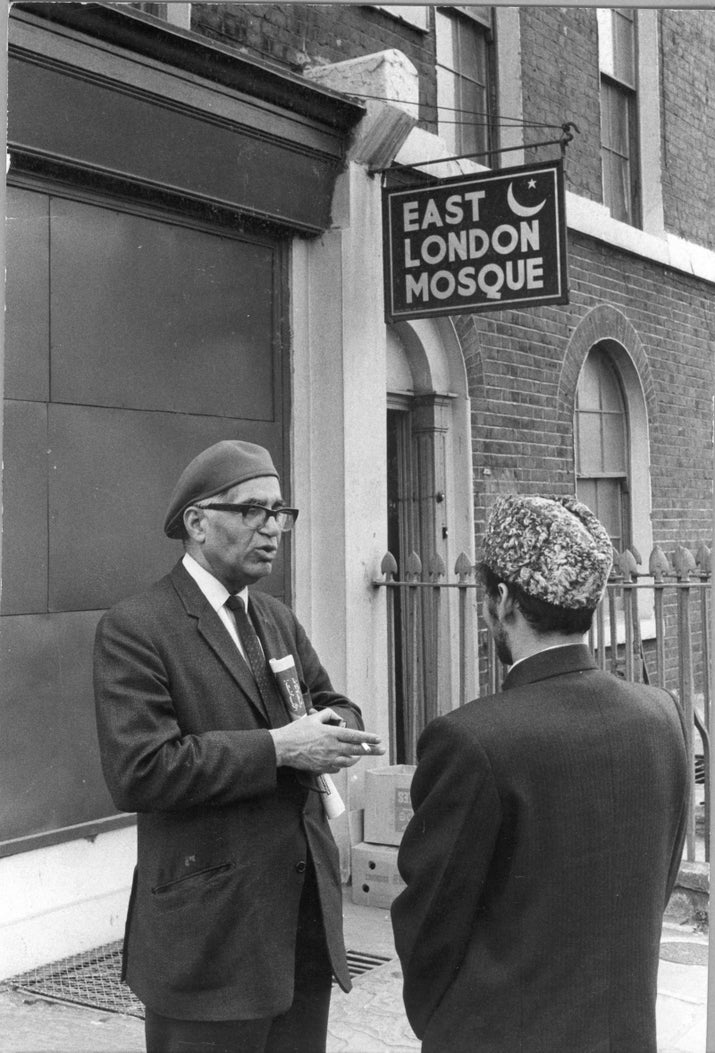 Two men talking outside the East London Mosque on Commercial Road, 1972. The Greater London Council, under compulsory purchase order, acquired the three mosque buildings on Commercial Road and in return provided land and temporary buildings (45 Fieldgate Street E1) until a permanent Mosque could be built on Whitechapel Road.