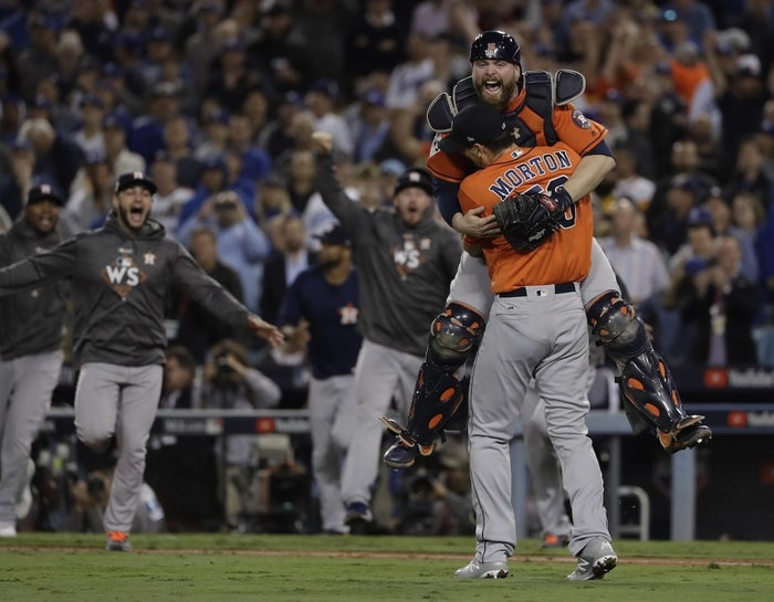 Houston Astros catcher Brian McCann leaps in the arms of starting pitcher Charlie Morton after winning the World Series.