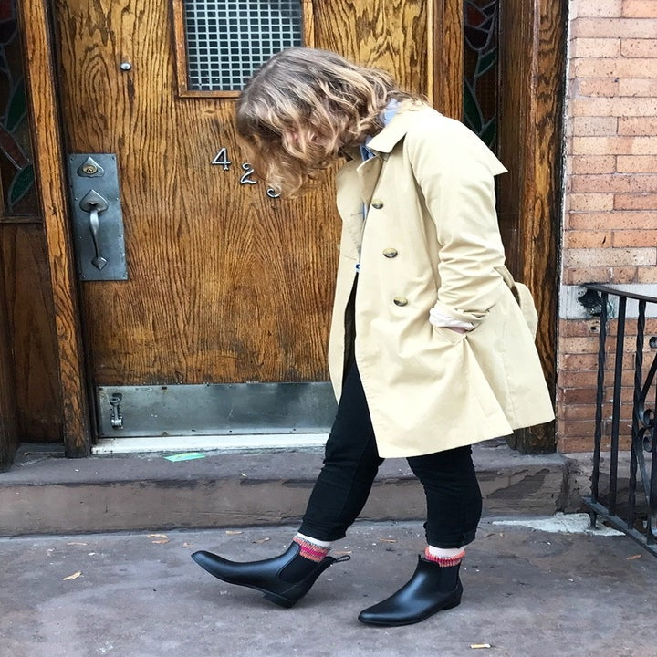 BuzzFeed editor, Rebecca O'Connell wearing the black rain boots with a trench coat outside