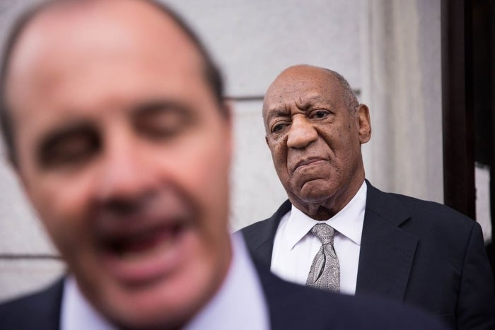 Bill Cosby looks on as his lawyer addresses the media.