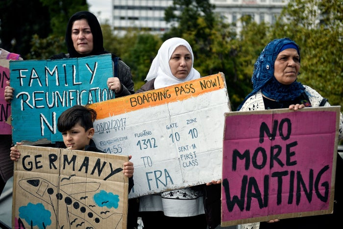 Refugee families carry signs during a protest against delays in reuniting with their relatives.