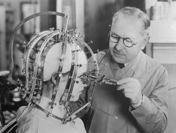 Contrary to what this may look like, this is just him taking measurements of a young woman's head and face with a slightly odd-looking contraption.