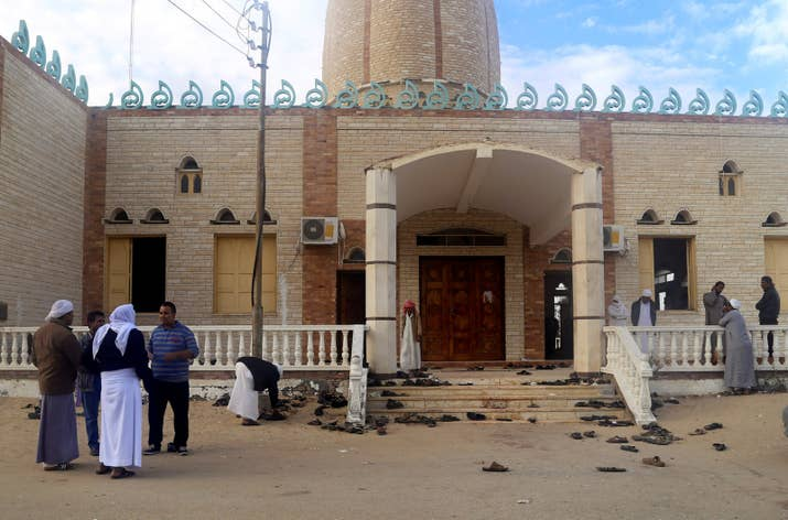 People stand outside Al Rawdah mosque, where a bomb exploded.