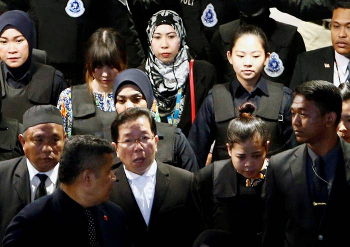 Doan Thi Huong (back, second from left) and Siti Aisyah (front, second from right), who are on trial for the killing of Kim Jong Nam, the estranged half brother of North Korea's leader, are escorted as they revisit the Kuala Lumpur International Airport 2 in October.