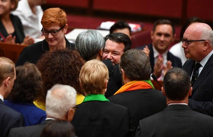 Senators celebrate after the same-sex marriage bill passes 43-12.