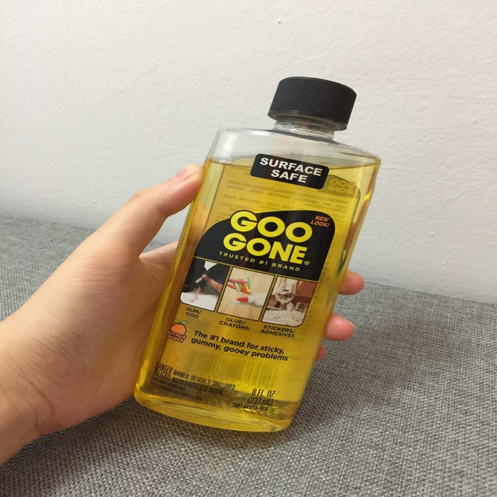 former buzzfeeder yi yang holds bottle of yellow liquid that says goo gone
