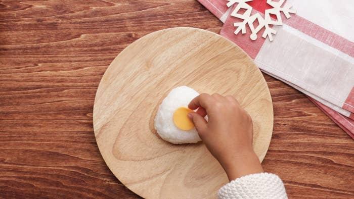 1人分材料:ごはん 150gカニ風味かまぼこ 3本スライスチーズ 1枚塩 ひとつまみのり 少々作り方1. 水で手を濡らし、塩ひとつまみを手に広げる。炊きたてのご飯を適量のせ、三角形に握る。2. カニ風味かまぼこの赤い部分を剥がし、白い部分も赤い部分と同じくらいの厚さになるように剥がす。赤い部分をストローで抜いて鼻を作る。3. スライスチーズをペットボトルの蓋で抜いて直径2cmくらいの円形にする。4. のりをカットして目を作る。5. (1)のおにぎりに(3)のスライスチーズ、(2)のカニ風味かまぼこの赤い部分、白い部分の順にのせる。6. (4)の目をつけたら、完成!