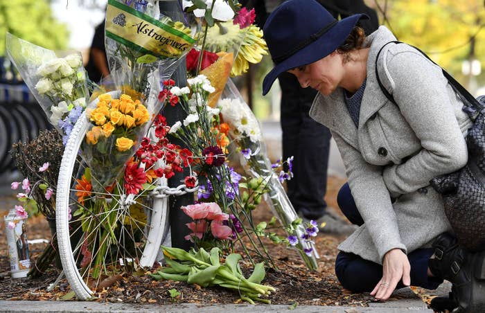 Flynn Coleman wipes away debris on Nov. 1 from an existing bicycle memorial that is now being used to mark the deadly attack during which Sayfullo Saipov, an Uzbek immigrant, drove a rental truck down a bike path for 20 blocks, killing eight people and injuring several more.