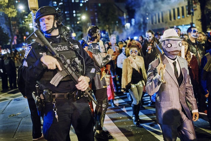 A heavily armed police officer stands watch as revelers march during the Greenwich Village Halloween Parade on Oct. 31 in New York.