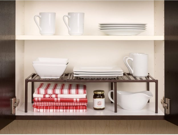 An expandable cabinet shelf for twice(!) the space to group like with like — i.e. all the white mugs can live separately from the rando initial mugs people keep giving you from the Anthro sale section.