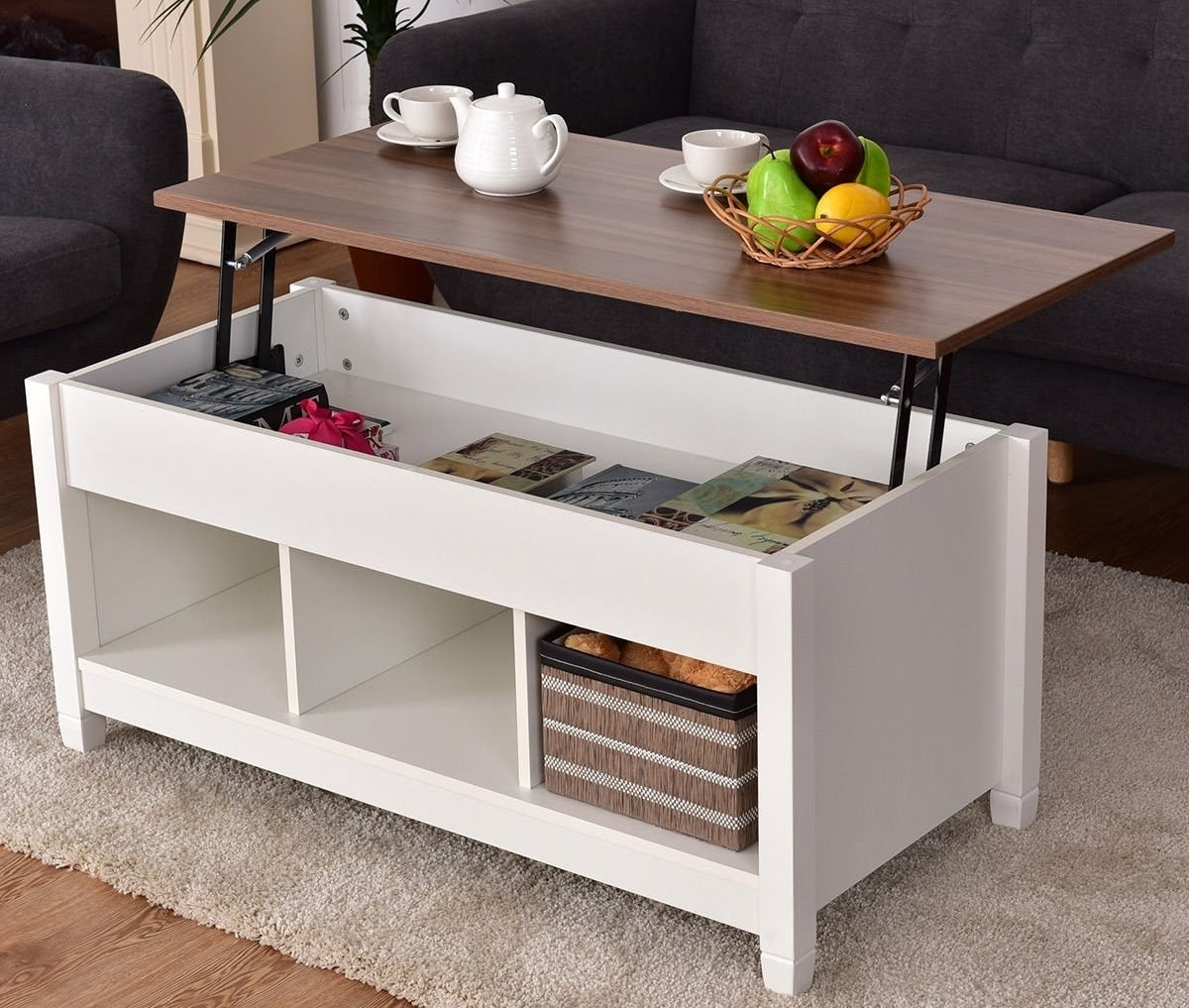 the lift top coffee table opened with books and snacks inside