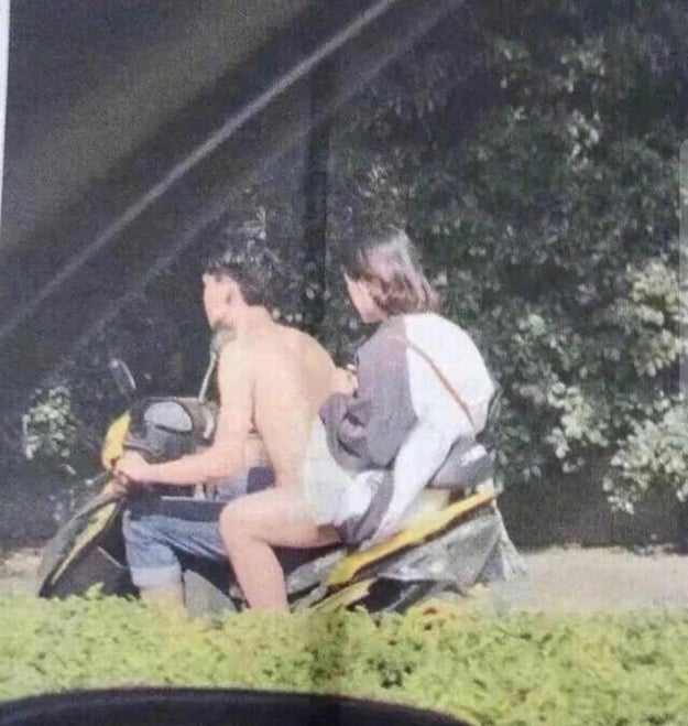 This naked man riding a motorcycle.