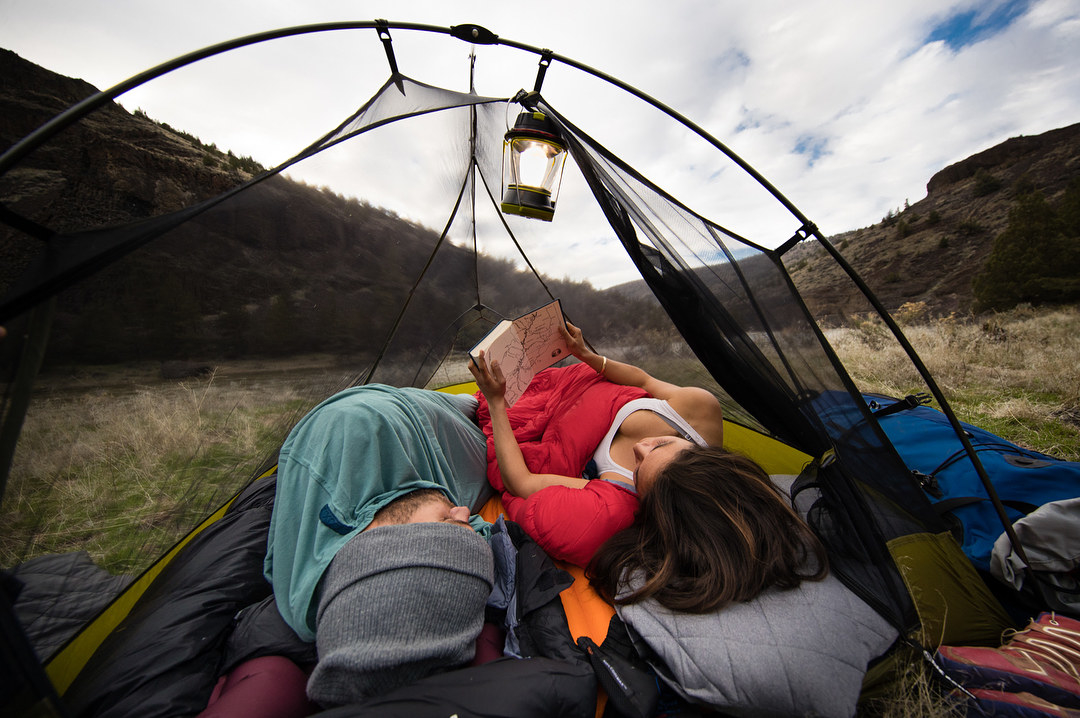 a couple laying in a mesh tent in what looks like a park