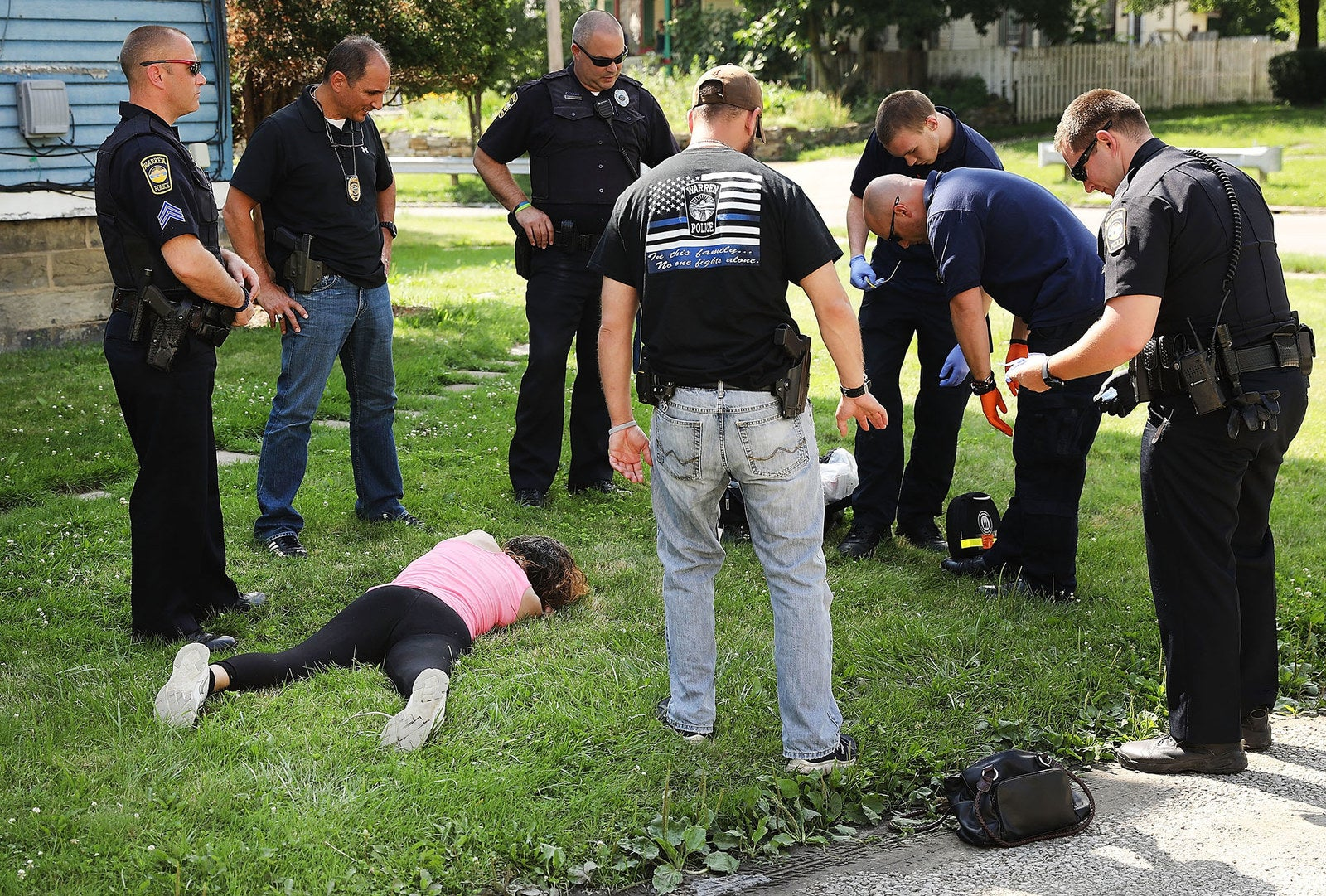 Medical workers and police treat a woman who has overdosed on heroin on July 14 in Warren, Ohio.