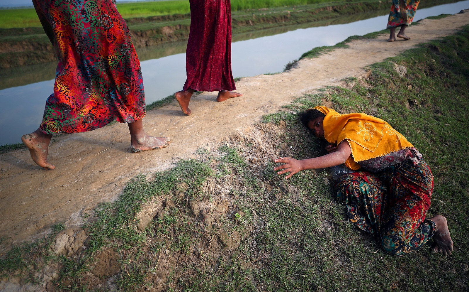 An exhausted Rohingya refugee cries for help to other refugees as they make their way from Myanmar into Palang Khali, near Cox's Bazar, Bangladesh, on Nov. 2.