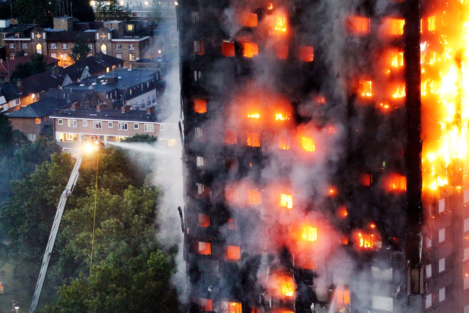 As dawn breaks, flames continue to leap from every window as over 200 firefighters from across London fought to tackle a blaze at the Grenfell Tower on June 14.