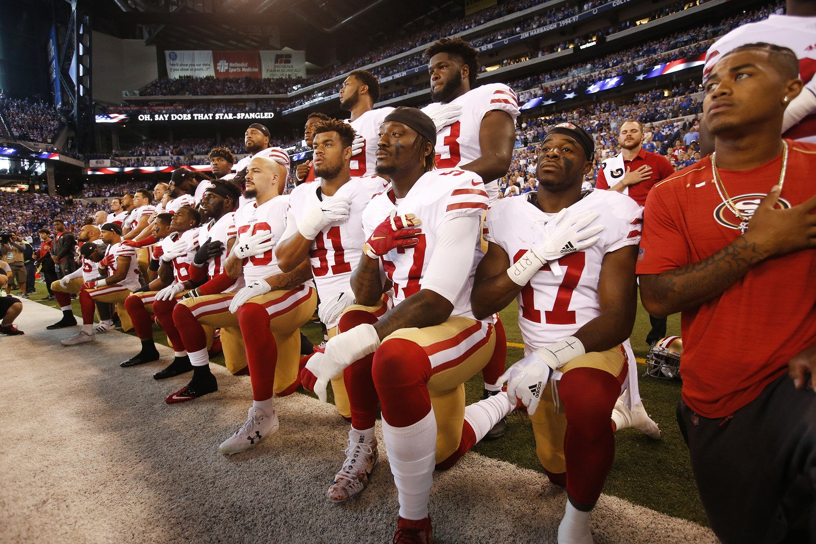 The San Francisco 49ers kneel and stand together during the anthem prior to the game against the Indianapolis Colts at Lucas Oil Stadium on Oct. 8, in Indianapolis.