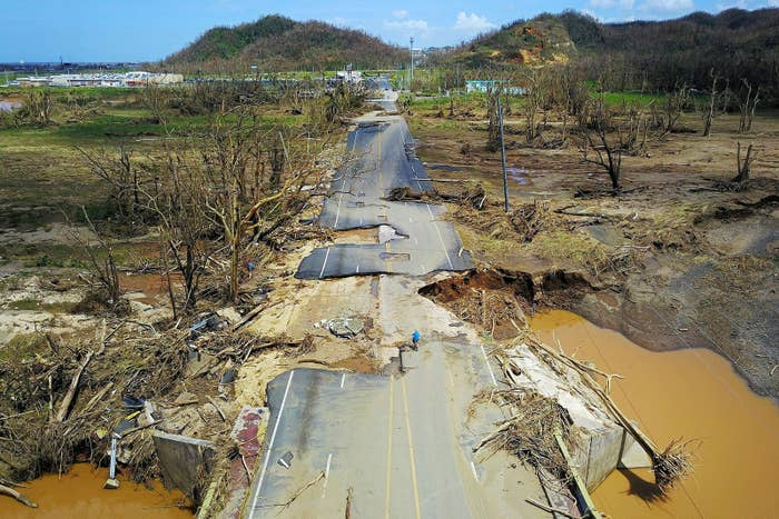 A man rides his bicycle through a damaged road in Toa Alta, west of San Juan, Puerto Rico, on Sept. 24, following the passage of Hurricane Maria.