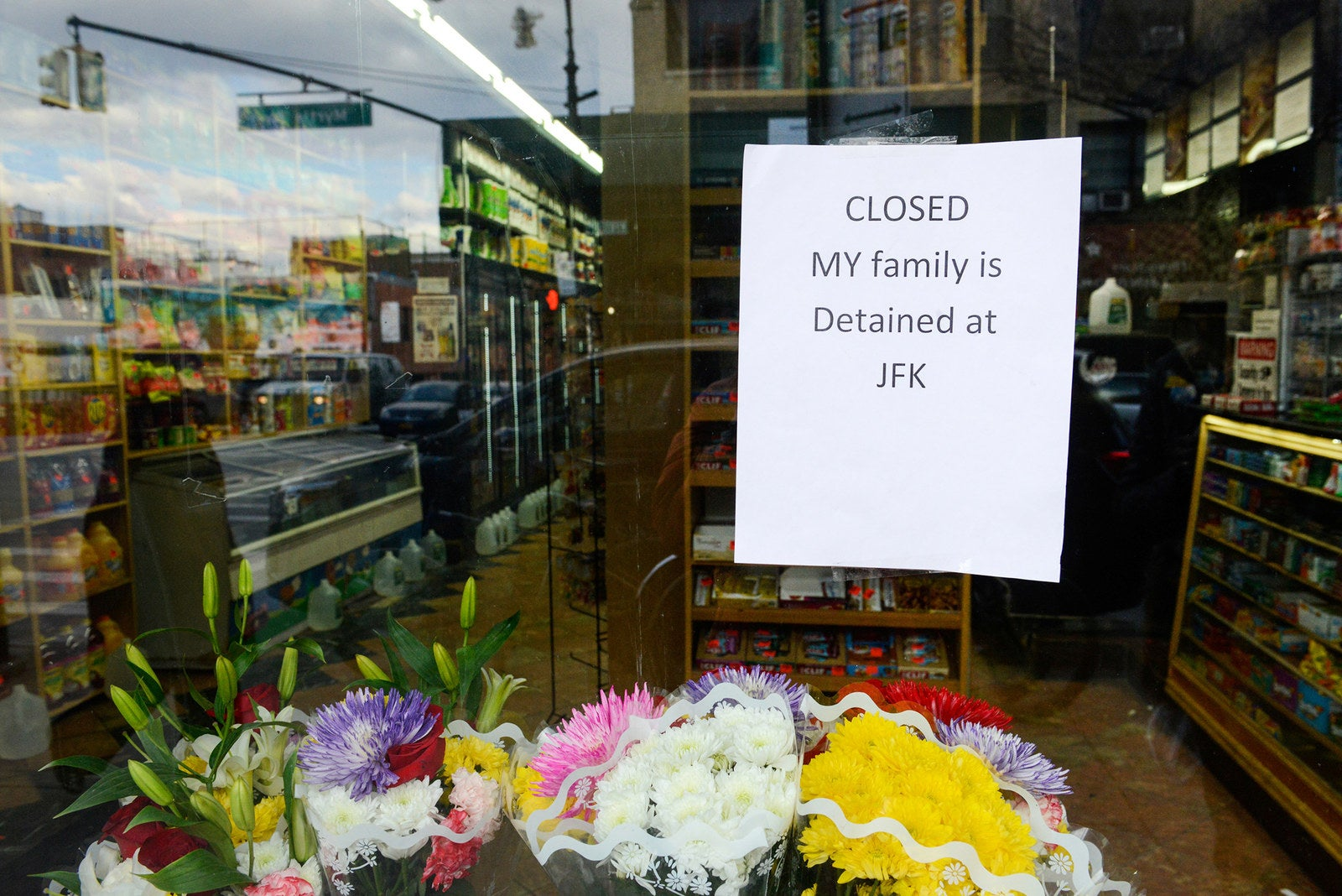 """A sign saying """"My family is detained at JFK"""" hangs in the window of a closed bodega during a Yemeni protest against President Donald Trump's travel ban in Brooklyn on Feb. 2."""